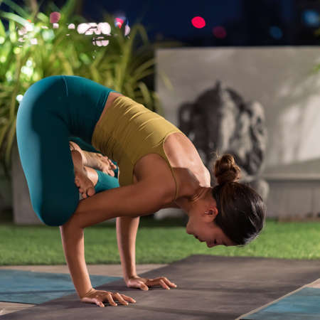 Asian female woman in sportswear bra pants practicing yoga during city lockdown alone in her apratment with background of cityscape illumination at night. Work out fitness healthy lifestyle concept.