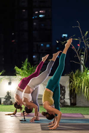 Group of asian women in sportswear pants practicing yoga during city lockdown in their apratment with distance in background of cityscape illumination night. Work out fitness healthy lifestyle concept