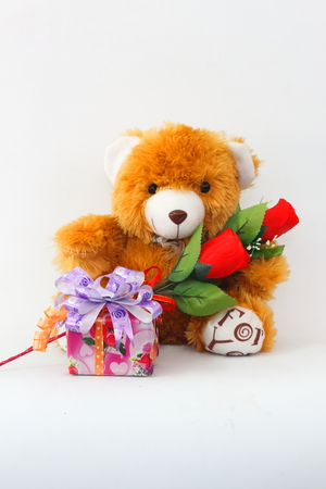 Brown teddy bear with a red rose and a gift box on a white background.