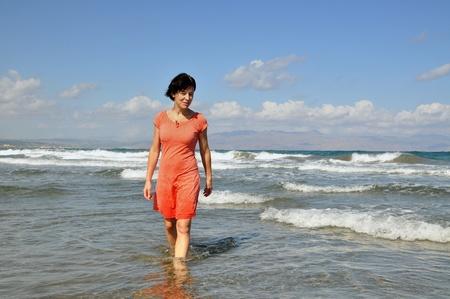 Smiling woman walking in tropical water