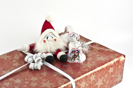 Christmas present with a santa doll and some jingle bells on top Stock Photo