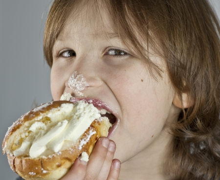 Boy enjoying a cream bun with almond paste getting cream on his noose.