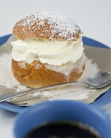 Cream bun with almond paste on a plate with a cup of coffe in front Stock Photo