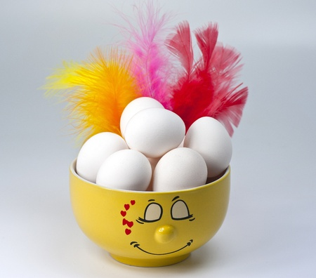 easteregg: Some eggs in a yellow bowl accompanied by some colorful feathers