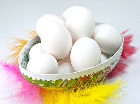 White eggs in an Easter egg surrounded by colorful feathers