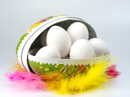 Closeup of white eggs in an Easter egg surrounded by colorful feathers