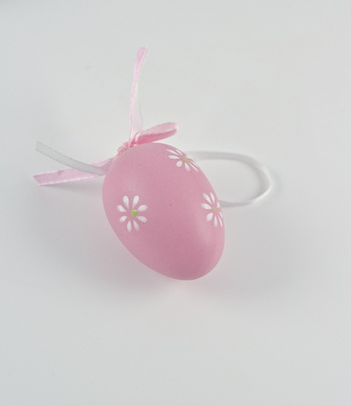 Single pink Easter egg with flower on lightgrey background Stock Photo