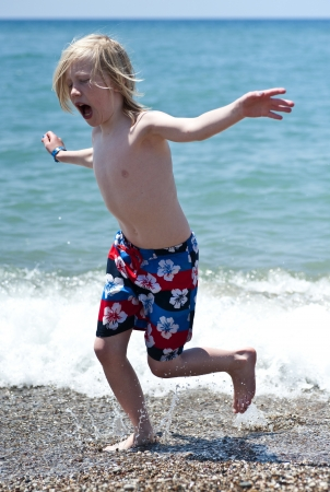 Young boy running in water