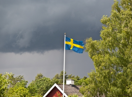 Thunderstorm coming on towards an idyllic little swedish house  photo