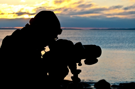 Silhouette of a birdwatcher looking out over the ocean at sunsetsunrise