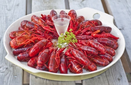 A plate filled with crawfish and a schnappas placed on an old table outdoors Imagens