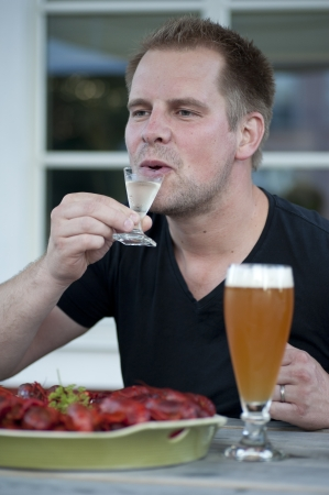 A male person enjoying a schnapps togehter with some crawfish. Stock Photo