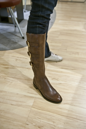 A female person trying on a pair of brown boots in a shop