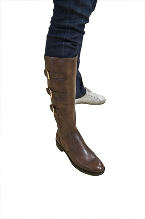 A female person trying on a brown boot isoltaed on a white background