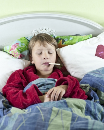 Young caucasian boy in bed with a thermometer in his mouth to check if he has fever