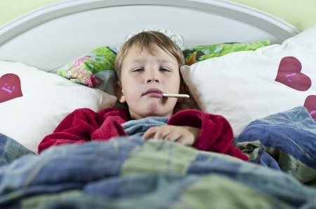 Young caucasian boy in bed with the flu checking if he has any fever Stock Photo