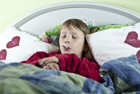 Young caucasian boy in bed with a thermometer in his mouth to check if he has fever Stock Photo - 15865689