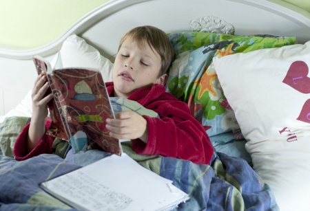 Young caucasian boy iIn bed with the flu doing schoolwork Stock Photo - 15865707
