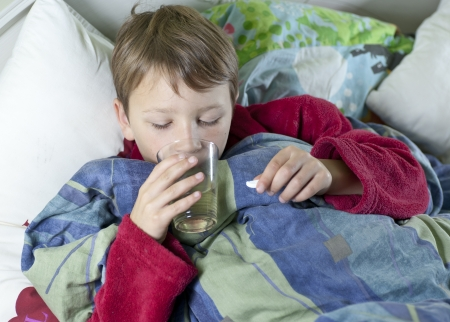 Young caucasian boy in bed with the flu taking his medicin