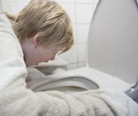 convulsion: Chico joven con gripe estomacal v�mitos en el ba�o Foto de archivo