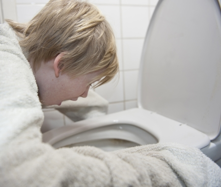 vomiting: Young boy with stomach flu vomiting in toilet