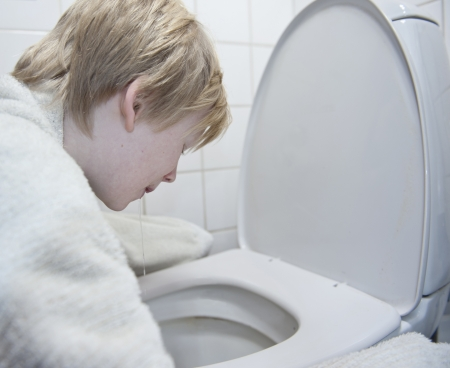 Young boy with stomach flu vomiting in toilet