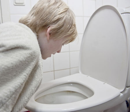 convulsion: Young boy with stomach flu vomiting in tolilet Stock Photo