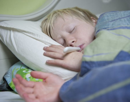 Boy in bed sick with a thermometer in his mouth