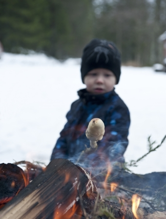 Young boy baking scones or bread on a stick over an open fire at wintertime