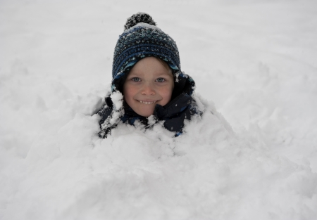 snow covered mountain: Young and cute smiling boy covered with snow