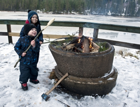 Young boys baking bread on a stick outdoors over an open fire at wintertime Stock Photo