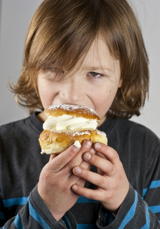 Young boy enjoying a cream bun with almond paste