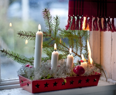 Burning candles in advent candle wreath setting fire on a curtain Imagens