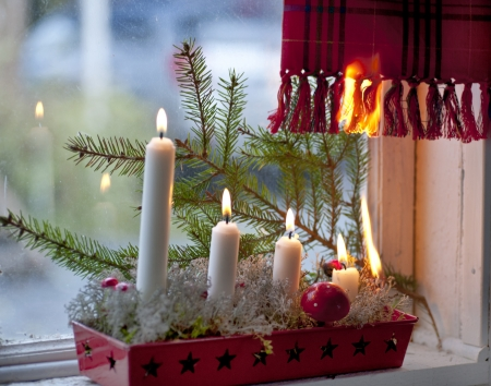 smoke alarm: Burning candles in advent candle wreath setting fire on a curtain Stock Photo