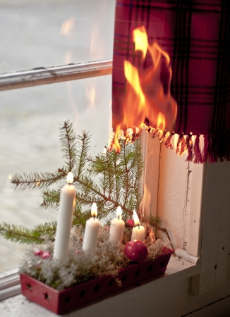 advent wreath: Advent candle wreath setting fire on a curtain Stock Photo