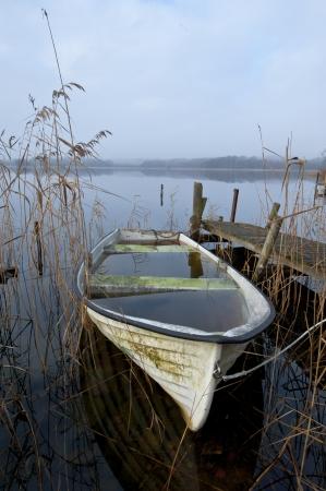 Abandoned boat at lake an misty november morning
