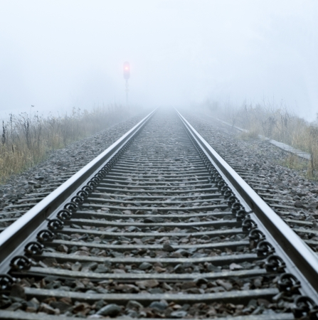 Railroad track in mist and a red signal