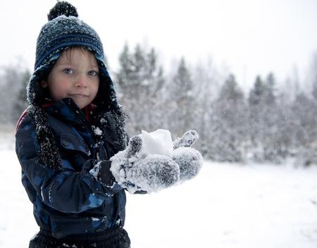 boule de neige: Jeune garçon essayant de faire une boule de neige