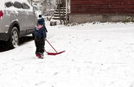 Young boy plowing away snow with a little shovel