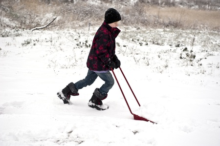 Young boy shoveling away snow with a shovel Stock Photo - 16671808