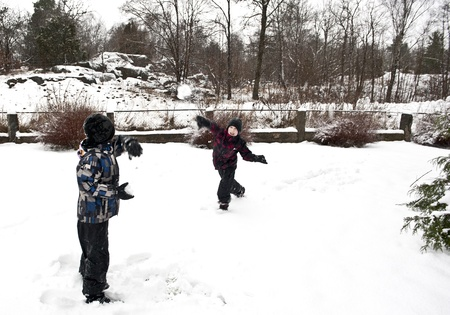 Children playing outdoors at winter time throwing snow balls at each other Stock Photo