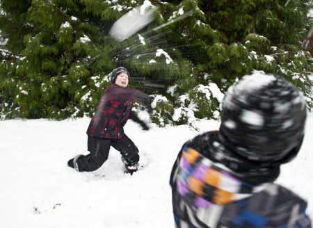 Children playing outdoors at wintertime throwing snowballs at each other