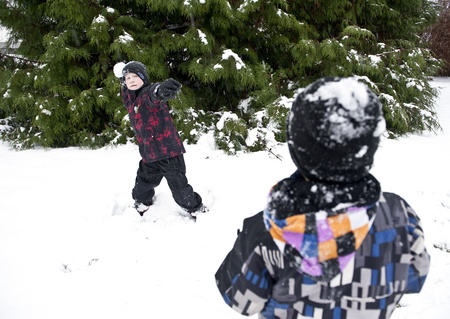 Children playing outdoors at winter time throwing snow balls at each other photo
