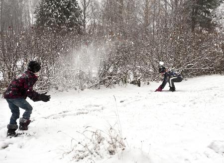 boule de neige: Enfants jouant � l'ext�rieur � l'heure d'hiver jeter des boules de neige � l'autre
