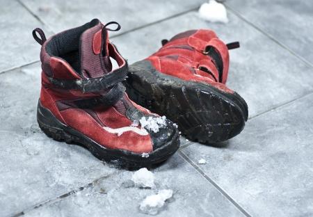 Een paar winterschoenen vol sneeuw waardoor de ingang vloer rommelig