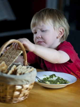 Young caucasian boy eating spinach soup and crispbread