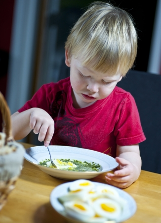 baby spinach: Young caucasian boy eating spinach soup with egg Stock Photo