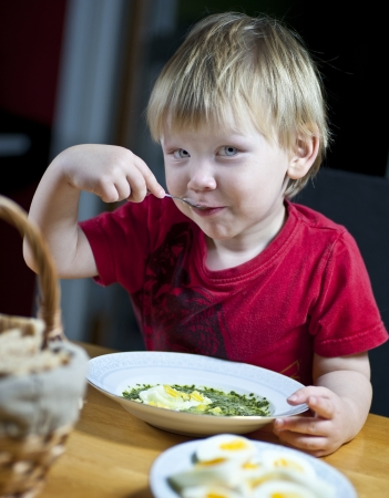 espinaca: Joven muchacho caucásico que come sopa de espinacas con huevo