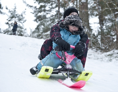 to steer a sledge: Two young boys going downhill on a modern snow sledge