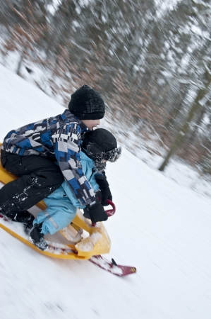 to steer a sledge: Two young boys going downhills on a modern snow sledge Stock Photo